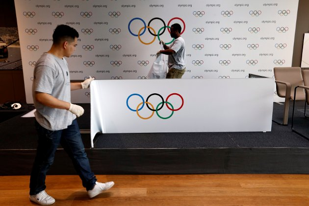Staff of the International Olympic Committee (IOC) dismantle a backdrop after a news conference after the Olympic Summit on doping in Lausanne, Switzerland, June 21, 2016.  REUTERS/Denis Balibouse