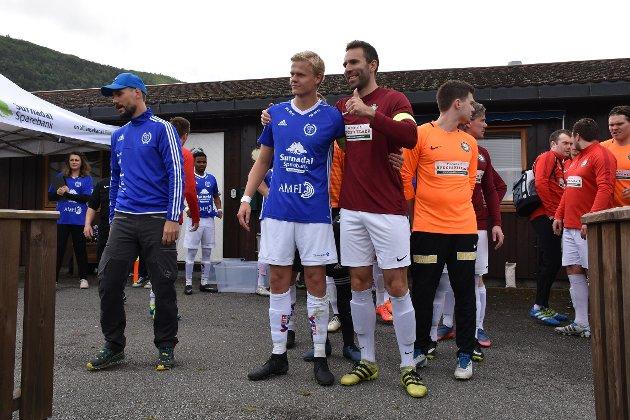 Kapteinene Vegar Brøske og Erik Liland leder sine lag inn på banen.