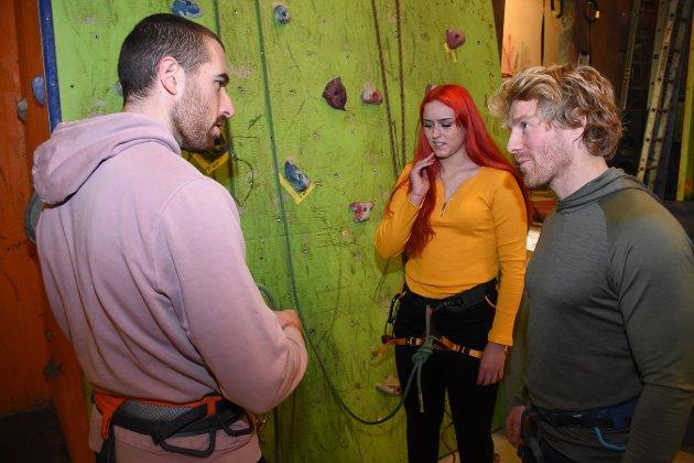 Instruktør Per Ola Thingvold (til høyre) forklarer Katarina Ekroll og Alex Gal hvordan man sikrer klatrekompisen.  - Jeg har aldri prøvd dette før, medgir Katarina.