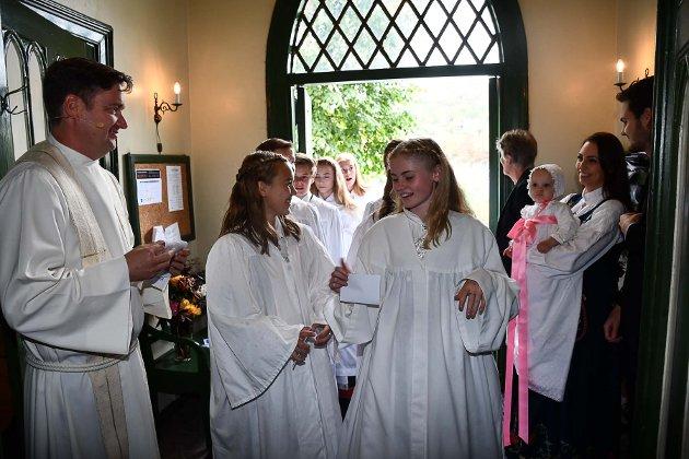 Konfirmantene gjør seg klare til å gå i prosesjon gjennom kirken. Marthe Bochmann og Tuva Dalen Aarstad først. Til høyre dåpsbarnet Sanna sammen med mamma, Christina Myrvin Olsen. Sokneprest Echard Graune til venstre.