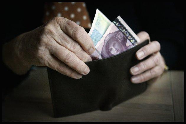 Sandvika 20040113. Eldre dame har tatt ut ut penger fra minibanken og står med lommeboken med penger i hendene, en tohundre og en etthundre seddel. Kanskje tenker hun på at pensjonskommisjonen la tirsdag fram sitt forslag til en fremtidig pensjonsordning som forhåpentligvis vil begynne å virke fra 2010. Pensjonister. Økonomi. Privatøkonomi. Lommebok. Pensjonist. Alderdom. Foto: Tor Richardsen / SCANPIX