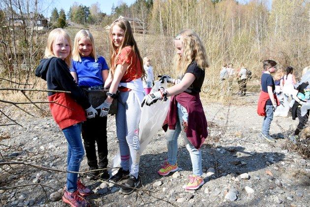 Harpefoss-elevene Pernille Bjerkehagen, Jenny Marie Nystuen, Lea Tvete Rolstad og Oline Amundsen hjelper hverandre med batteriet de fant ved elva på Harpefoss.