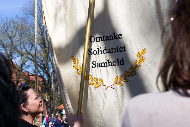 Omtanke, Solidaritet og Samhold sto det på baksiden av en av fanene. Veronica Vang holdt fanen, og ser her ut til å tenke nøye igjennom ordene.