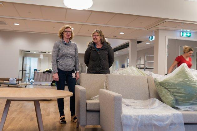 Gunn Sandvik og einingsleiar for pleie og omsorg, Margunn Lægreid, i den nye arbeidsstova. Den nye bygdaheimen har fleire stover og avdelingar enn den gamle, dermed må ein òg ha fleire møblar. Bak dei er produksjonskjøkenet med serveringsdisk.