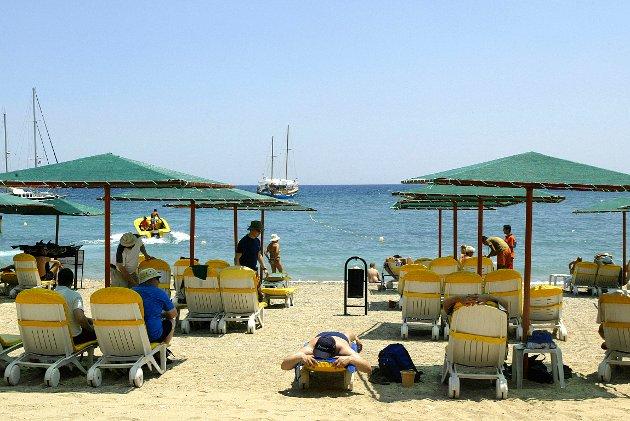På ferie til Tyrkia. Turister ligger i solsenger på stranden eller sitter under parasoller. Foto: Håkon Mosvold Larsen / SCANPIX
