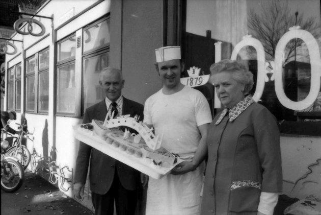 8. november 1979:  Bedrifter  Ivar Halvorsen Bakeri  Vestfolds eldste bakeri markerer sine hundre år.  Josef Lang, Hans Martin Lang og Randi Røed (kontordame) utenfor hovedforretningen på Hvidts plass. Bryllupskaken som Hans Martin Lang holder, har vært en stor suksess siden den ble lansert for 35 år siden.