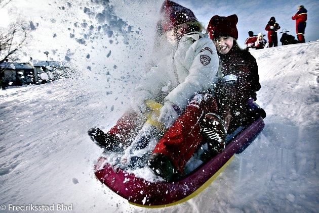 Vinterferie-aktiviteter: Førsteklassingene Victoria René Kulås Jørgensen (foran) og Mathilde Gudesen aker i bakken utenfor Trosvik skole. Foto: Nils Harald Ånstad, 20.02.2006