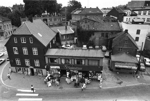 """Skoggata 2, 1984. Til høyre i bildet ser vi kiosken «Festusbua» og i midten ser vi klesforretningen """"Ernst & Einar» som ble drevet av fotball-profil Einar Aas og kameraten Ernst Halvorsen. Til venstre for denne var det kiosk (Frukt og tobakk) i kjellerlokalet. I bakgrunnen skimtes blant annet øvre torg med Basarbygget og apoteket i Kongensgate. Til venstre i bildet er Torggata."""