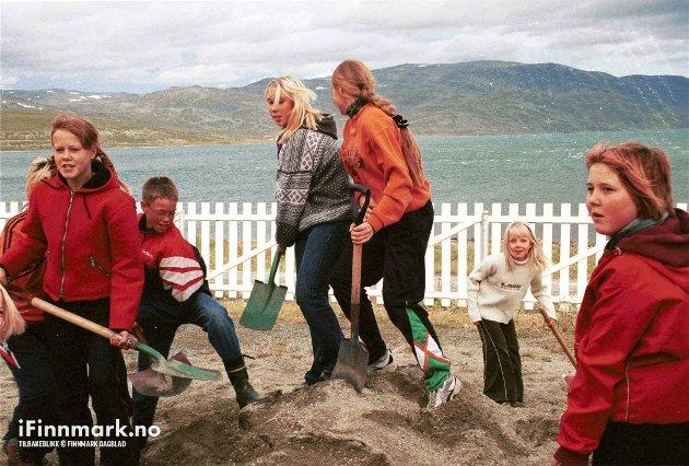 90-TALLET: Elevene jevner sand under lekeapparatene i skolegården på Kvalsund skole.