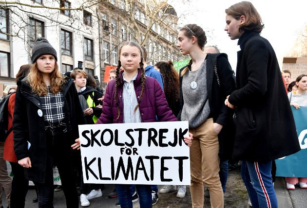 """In this Thursday, Feb. 21, 2019 file photo, Swedish climate activist Greta Thunberg, center, holds a sign which reads: 'school strike for the climate' during a climate march in Brussels. Germany's foreign minister Heiko Maas says that about one year after Thunberg first staged a protest in front of the Swedish parliament he's """"grateful"""" for her climate protests. (AP Photo/Geert Vanden Wijngaert)"""