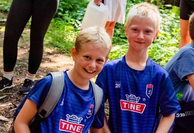 Kameratene Kristian (11) til venstre og Olle (11) deltar på Tine fotballskole, men med litt overlapping får de også med seg fire dager på Ås sommeridrettsskole. Her er første dag ute i skogen.