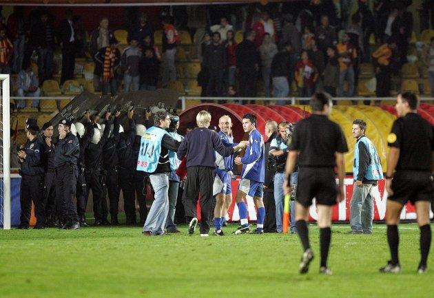 Roar Christensen og Lars Iver Strand gliser etter kampslutt, mens politiet lager skjold.