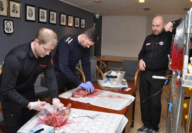 Jim Daniel Pettersen (fra venstre) og Roger Thorsen øver her på å stopp blod på et stort kjøttstykke som får tilført kunstig blod. Instruktør Geir Ingebrigtsen til høyre.