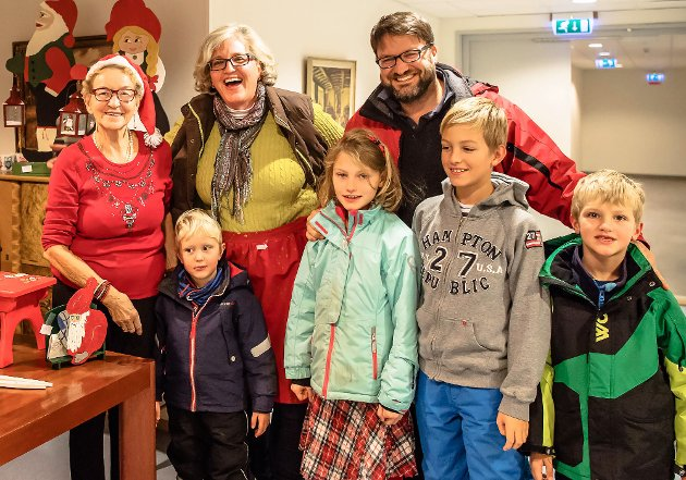 Bjørg på Nordby eldresenter selger rødt juleforkle til nabo Delsa Ivanov og mannen Nik, og barna Oscar, Elni, Christian og Alexander.