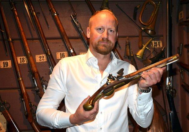 STOLT EIER: Dagens eier av gården, Hans Ener Østberg, viser stolt fram en flintlåspistol fra Tordenskilods tid på 1700-tallet. Dette er det eldte våpnet blant de omkring 200 historiske våpnene på gården.