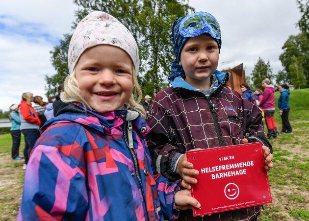 Barnehagene i Rana er kåret til Helsefremmende barnehager. Ida Josefine Snefjellå og Thomas Nyborg fra Kirkebakken kulturbarnehage med det flotte skiltet.
