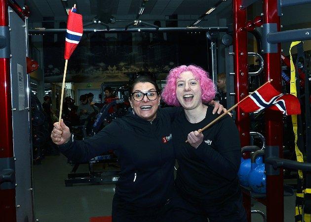 VERDT Å FEIRE: – Dette er en gledens dag verdt å feire med norske flagg. Nå håper jeg virkelig vi slipper å stenge ned flere ganger. Dette har vært tøft for vår bransje, så nå håper jeg det retter seg for dette har vært det tøffeste jeg har vært med på. Vi har for øvrig hatt veldig bra besøk helt fra grytidlig morgen i dag, forteller daglig leder Nina Kjoshagen i Family Sports Club Mysen mens hun vifter med flagg sammen med datteren Julie Kjoshagen.
