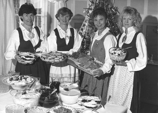 Disse damene viser fram julemat på starten av 90-tallet. Marit Løvbrøtte hos Matprat forteller at disse damene var ansatt ved Opplysningskontorene i landbruket. Ingen av dem er fra Hadeland, og bildet var nok sendt med i forbindelse med pressemelding. Fra venstre er et Anna-Karin Lindstad, Guri Tveit, (ukjent) og Kari Jørgensen.
