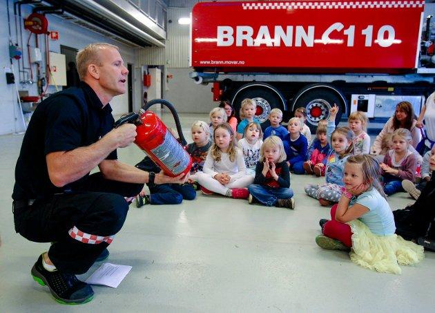 Barnehagebesøk på Moss brannstasjon. Christian Ellingsen viser frem et pulverapparat.
