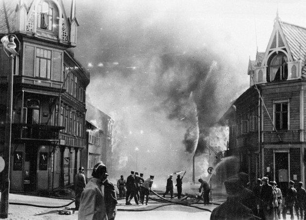 Krigen i Norge etter tyskernes overfall. Narvik i brann etter tysk flyangrep 1. juni 1940. Bygate med brennede hus, brannslukning. WW2 - Norway / Narvik. German air attack,  burning houses after bombing.