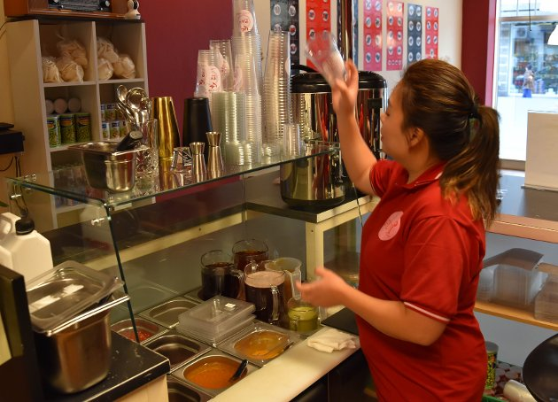 VELGE SMAK: Først må kunden velge seg en av mange smaker. Vi får Thanh Tran til å lage bestselgeren boble-te med fersken. FOTO: Vibeke Bjerkaas