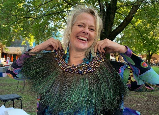 PÅFUGL: Elfi Sverdrup viser smykker som hun på finurlig vis har laget av tynt svineskinn, som er belagt med metaller og farger, før de får et lag med gulvlakk for å holde. Her holder hun frem en klave i påfuglfjær og glassperler. Den er den eneste i sitt slag. Hun lager også lydsmykker.