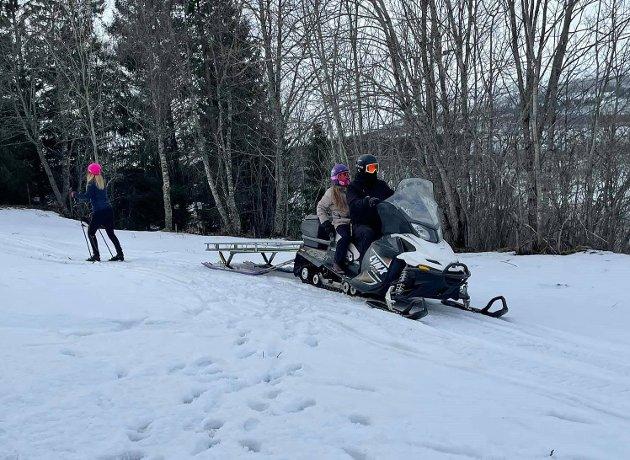 Skiløpere og scootere side om side i naturen.