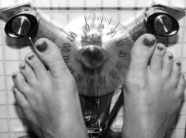 Et par føtter med rød, avskallet neglelakk på tærne. Slitne føtter. Veier seg. Står på badevekt. Spisevegring. Vektproblemer. Vekt. Overvekt. Spisevaner.    Foto: NTB