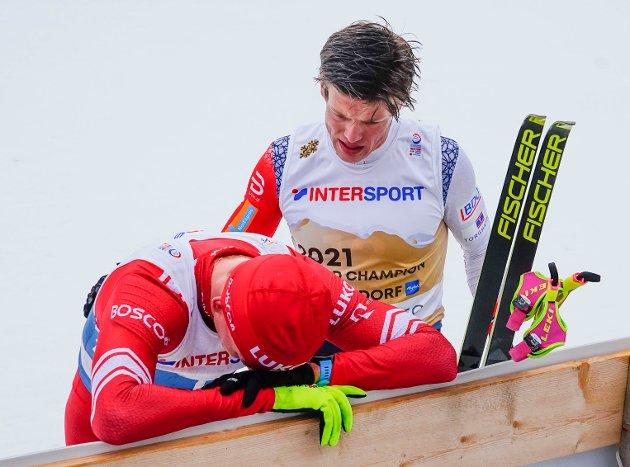 Johannes Høsflot Klæbo og en skuffet Aleksandr Bolsjunov fra Russland etter en dramatisk innspurt med stavbrekk under langrenn 50 km for menn under VM på ski 2021 i Oberstdorf, Tyskland. Foto: Lise Åserud / NTB