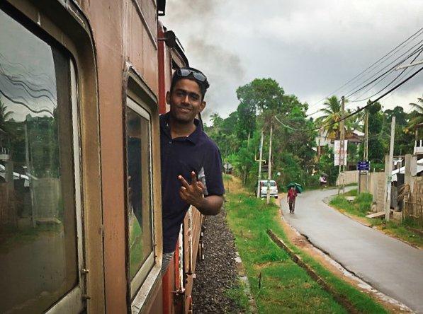 LANGS SKINNENE: Sri Lanka`s kollektivtransport er en turistattraksjon i seg selv med åpne vinduer og ikke-eksisterende dører. Shehan titter ut fra nabovognen.