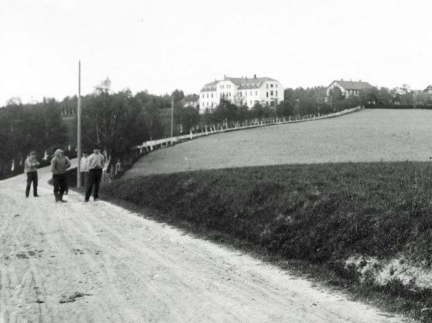 Dette bildet av Kalnes landbruksskole med noen av elevene på veien inn til skolen ble tatt av fotograf Anders Beer Wilse 1. mai 1907.