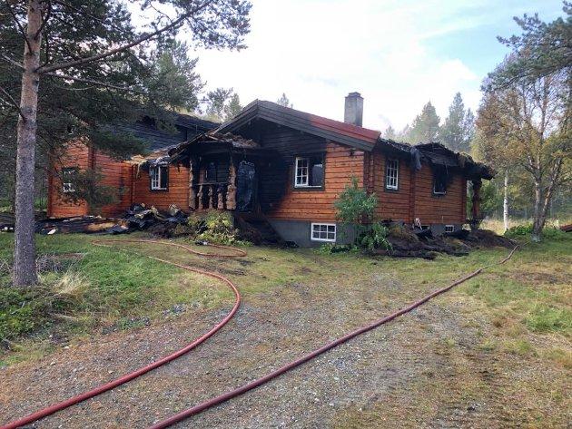 Fritidsboligen har fått store skader i brannen. Ved hjelp av gravemaskin ble torva tatt vekk slik at brannmannskaper skulle klare å slukke brannen i taket på hytta.