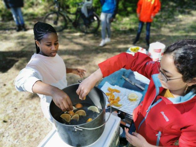 Zarah og Vanessa lager saft av løvetann, granskudd og sitrusfrukt onsdag formiddag i Urheia.