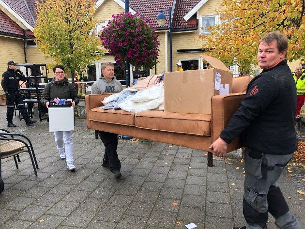 Travelt: Næringsdrivende og andre fikk det travelt med å bære ut møbler og varer fra lokalene i første etasje på Gressvik torv etter brannen. Vann fra slukningsarbeidet rant ned.