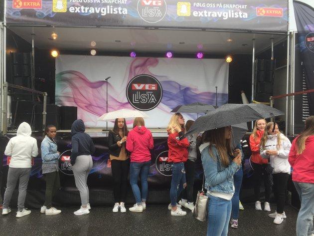 WAITING GAME: Tenåringsjenter trosset regnværet og paraplyene fylte scenen før Coop Extras roadshow.