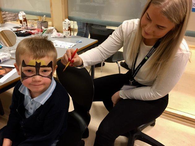 """BATMAN: Fem år gamle Magnus Holm ble helt Batman lørdag formiddag, han fikk ansiktsmaling av Tiril Jørgensen ved 2BA. Det var fullt kjør med unger som ville males, katt og Batman var mest populært, fikk vi høre. """"Åpen skole"""" ved Sentrum vgs hadde mange tilbud til de aller minste."""