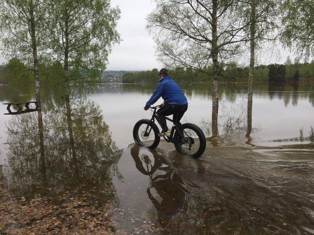 BRÅDYPT: Vannet stiger og Knut Rinden tester om det i hele tatt kan sykles, det renner mer og mer innover parkerings- og rasteplassen ved Norsenga og gamle Nor skanse.