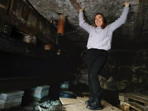 Lillian Nyborg ved Østfoldmuseene har sitt svare strev med å holde sviktende låvebruer og plankegulv ved like. Her i møkkakjelleren på Rød Herregård, der gulvet er midlertidig støttet opp for ikke å svikte.
