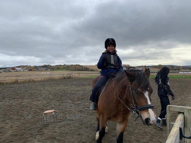 Sina Steiro (11) rir på hesten King (19)