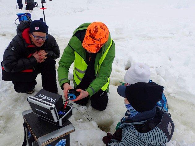 Herman Neple (med oransje caps) viser Jarle Lome, Birk Johan Lome og Daniel Sommer hvordan det ser ut på bunnen av Garsjø ved hjelp av et undervannskamera og dataskjerm.