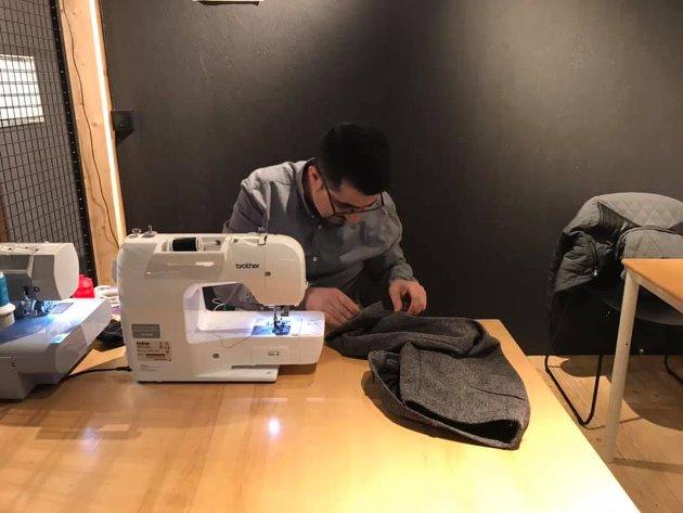 Ahmad Khalil reparerer klær på Veitasenteret i mars 2019.