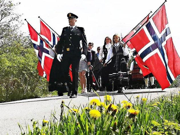 17. mai-toget kommer ned Kirkebakken i Skiptvet, og de norske flaggene vaier i det fine maiværet.