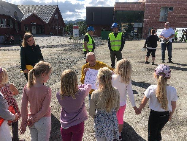 Ordfører Ingrid Waagen og byggekomiteleder Gunnar Waagen forklarer skoleelevene hvordan Nordmørshallen i Straumsnes blir.