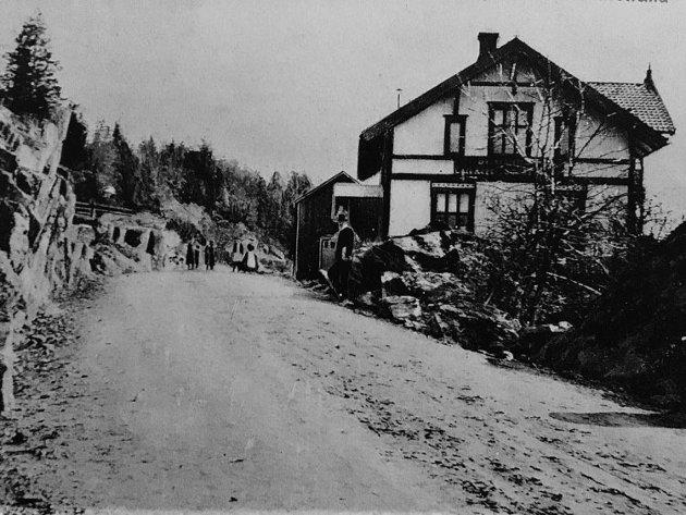 Med uthus mot veien: Bak Fødehjemmet skimtes uthuset som siden er flyttet lenger inn mot hagen, etter en veiutvidelse. Dette bildet skal være tatt rundt 1910, i følge lokalhistorisk entusiast, Morten Løvdal.