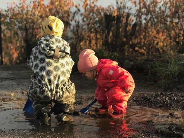 Barn som leker og koser seg i en vanndam