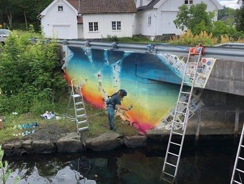 Her dekorerer kunstner Marius Martinussen brua ved Sagesund. Vegvesenet kan styre sin begeistring, men FrPs Silje Flaten Haugli synes det er flott.