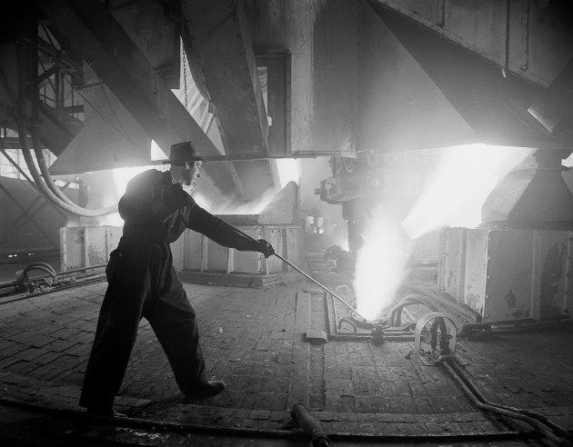 MO I RANA 1955 Norsk Jernverk i Mo i Rana er satt i drift. Interiør fra en av hallene.  Mann i arbeid med flytende stål. Foto: Sverre A. Børretzen / Aktuell / Scanpix