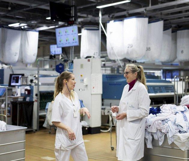 Teamkoordinator Michelle Eikeseth (til venstre) og seksjonsleder Anne Nielsen i vaskeriet på Haukeland sykehus, der det til sammen jobber rundt 50. Eget vaskeri har i praksis vist seg å bety svært mye for godt smittevern og god beredskap. Foto: Katrine Sunde