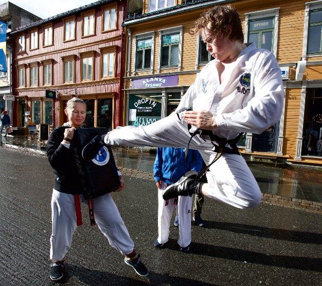 Sander Solhaug fra Polar Taekwondo, flyr høyt, og sparker til puta som Mina Bratterud Hansen holder frem.