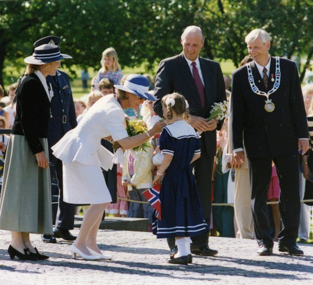 BYJUBILEUM 1995: Blomsteroverrekkelse fra en av byens unge innbyggere til Dronning Sonja. Kong Harald og ordfører Per Ramberg ved siden av.